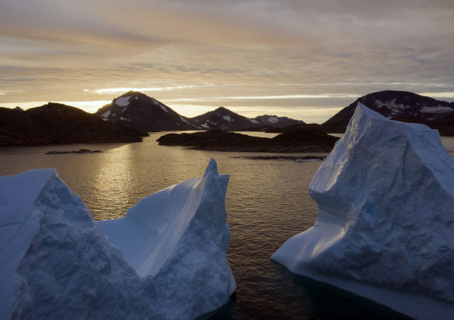 An aerial view of large Icebergs floating as the sun rises near Kulusuk, Greenland.