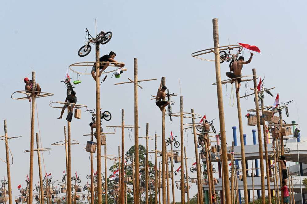 Participants climb greasy poles at a beach in Jakarta on August 17, 2019, during Panjat Pinang, a pole climbing contest to celebrate Indonesia's 74th anniversary of independence from Dutch rule.