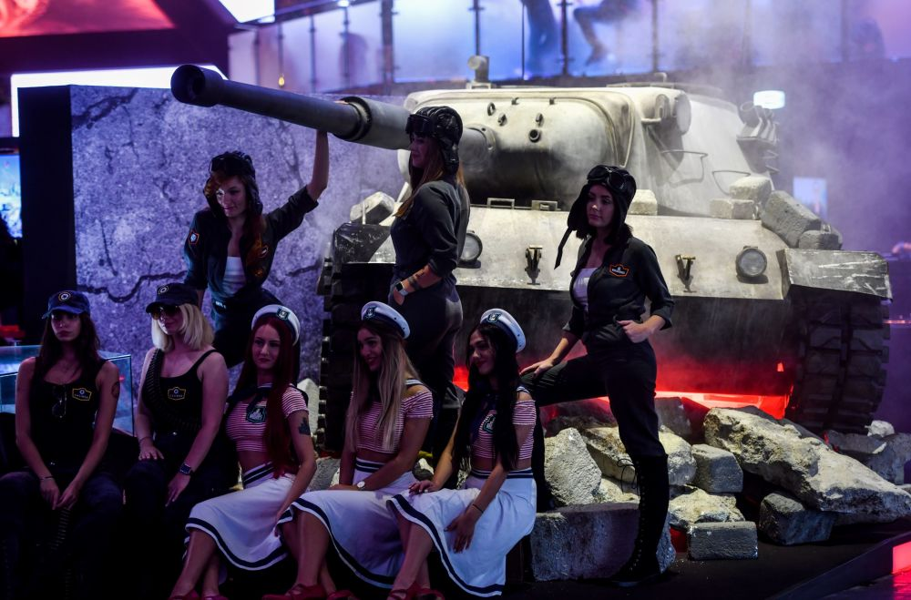Dressed girls stand on a tank during the Video games trade fair Gamescom in Cologne, western Germany, on August 21, 2019.