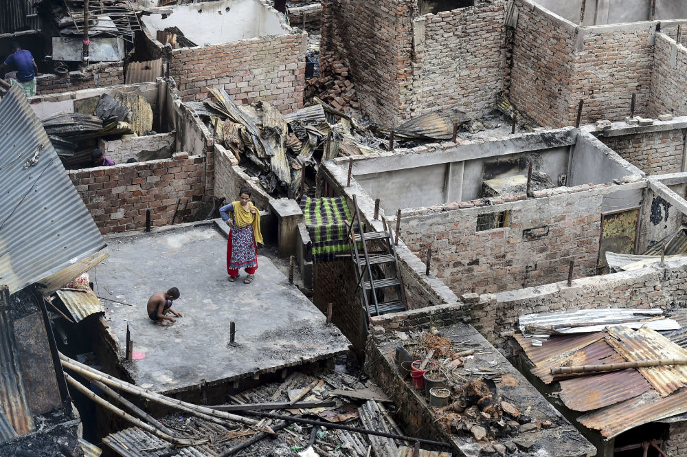 A child plays on a roof of a burnt house in a slum in Dhaka on August 18, 2019