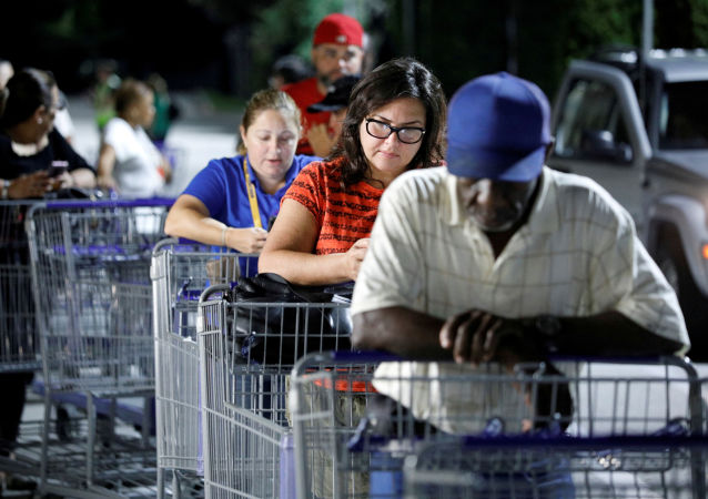Shoppers wait in line for a Sam's Club store to open before sunrise, as people rushed to buy supplies ahead of the arrival of Hurricane Dorian in Kissimmee, Florida, U.S. August 30, 2019