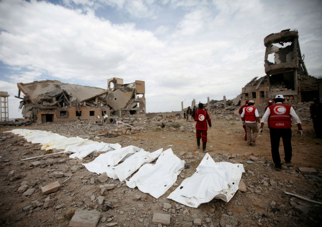 Red Crescent medics walk next to bags containing the bodies of victims of Saudi-led airstrikes on a Houthi detention centre in Dhamar