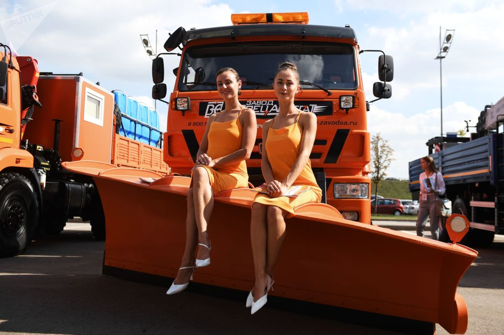 Promo models pose for pictures near KAMAZ vehicles at the Comtrans 2019 international car show in Moscow