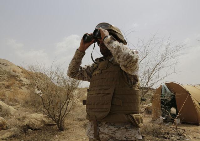 A Saudi soldier looks with binoculars toward the border with Yemen in Jazan, Saudi Arabia, Monday, April 20, 2015