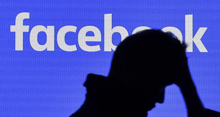 A man passes a facebook screen