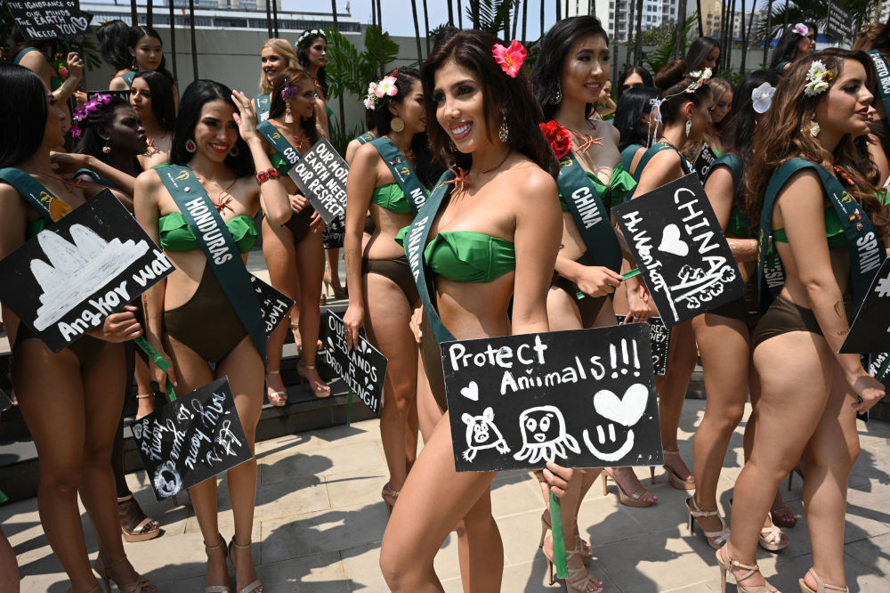 Miss Earth candidate Marrianna Fuentes (C) of Panama holds a placard with an environment theme as she poses with other Miss Earth candidates for photos during a press presentation at a hotel in Manila on October 2, 2019.
