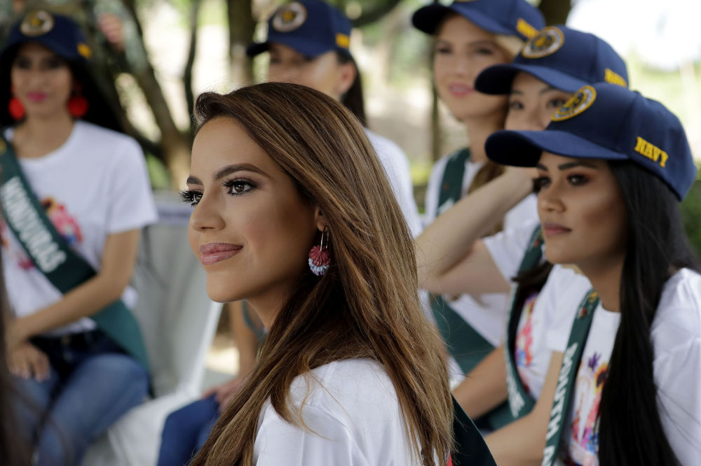 Sonia Romeo, center, of Spain, a candidate for the Miss Earth 2019 beauty pageant, listens to briefing prior to joining the Philippine Navy in conducting coastal cleanup, one of the activities lined up to call the attention to help save Mother Earth, Monday, Sept. 30, 2019 in suburban Las Pinas city, south of Manila, Philippines.