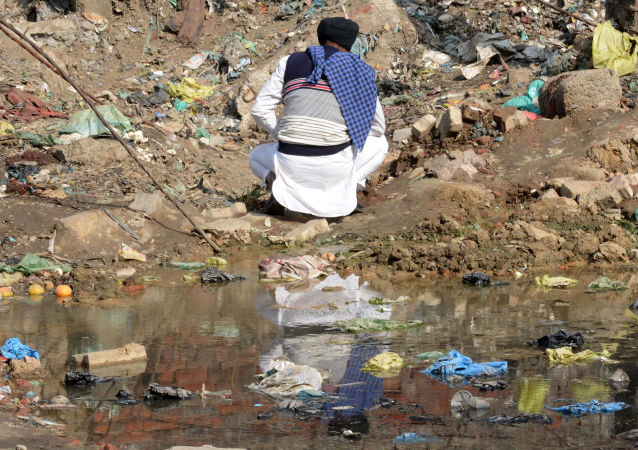 An Indian man urinates on the roadside in Amritsar on November 19, 2017