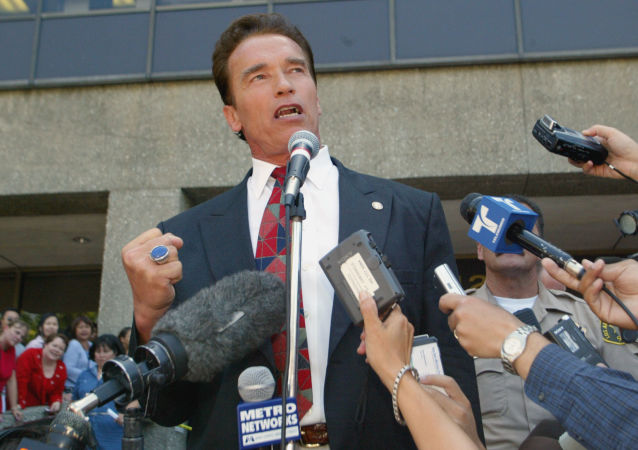 Arnold Schwarzenegger makes a fist will talking outside the Los Angeles County registrar's office in Norwalk. Calif., Thursday, Aug. 7, 2003, after picking-up candidacy papers for the California gubernatorial recall election slated for early October.