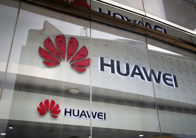 FILE - In this 29 January 2019 file photo, the logos of Huawei are displayed at its retail shop window reflecting the Ministry of Foreign Affairs office in Beijing