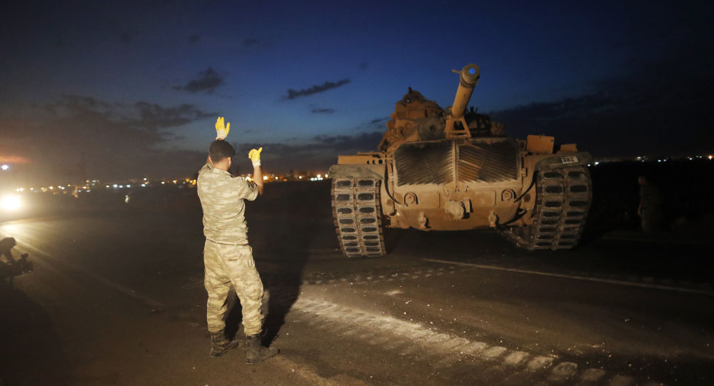 A Turkish army officer guides a comrade driving a tank to its new position, after was uploaded from a truck, on the Turkish side of the border between Turkey and Syria, in Sanliurfa province, southeastern Turkey, Tuesday, Oct. 8, 2019