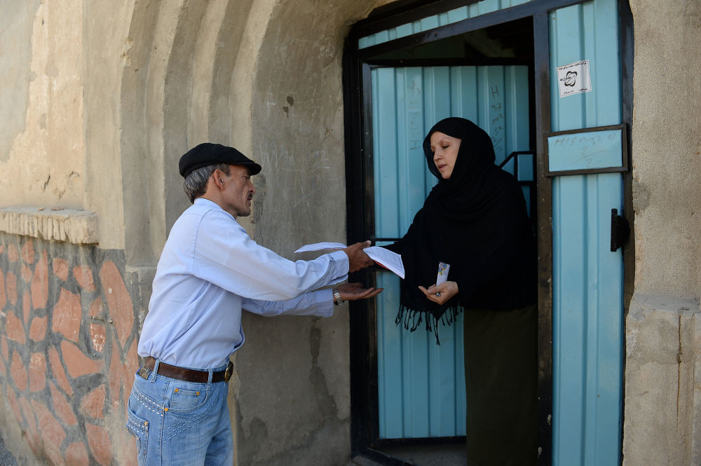 In this photograph taken on June 11, 2013, Afghan postman Mohammad Rahim delivers letters to a resident in the Kart-e-Sakhi neighbourhood of Kabul.