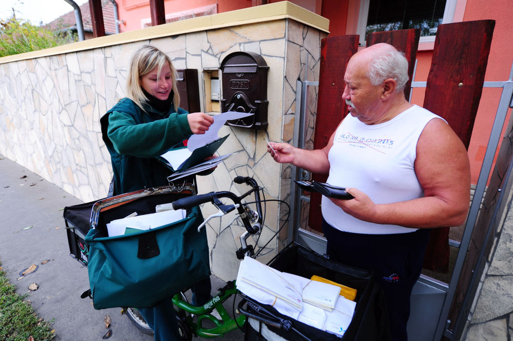 An official of the 'Magyar Posta' (Hungarian Post Company) Bernadett Kasza delivers a letter to a man in her district in Budapest on October 18, 2013.