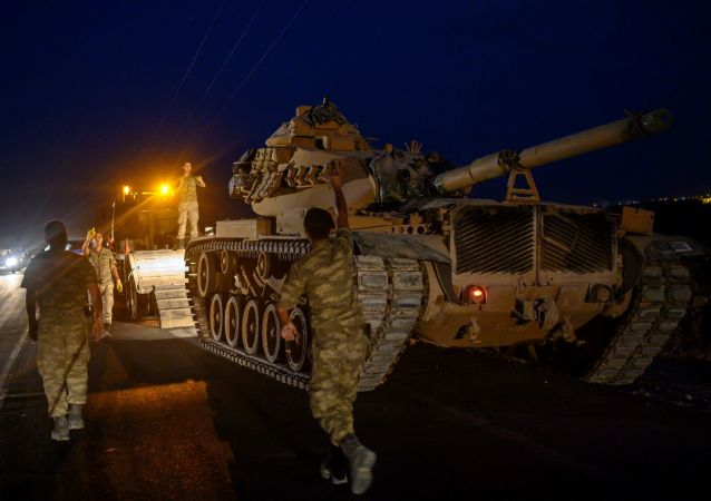 A Turkish army tank drives down from a truck as Turkish armed forces approach the border with Syria near Akcakale in Sanliurfa province on 8 October 2019