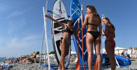 Female holidaymakers are getting ready for a sea surfing in Nizhneimeretinskaya Bukhta, Sochi.