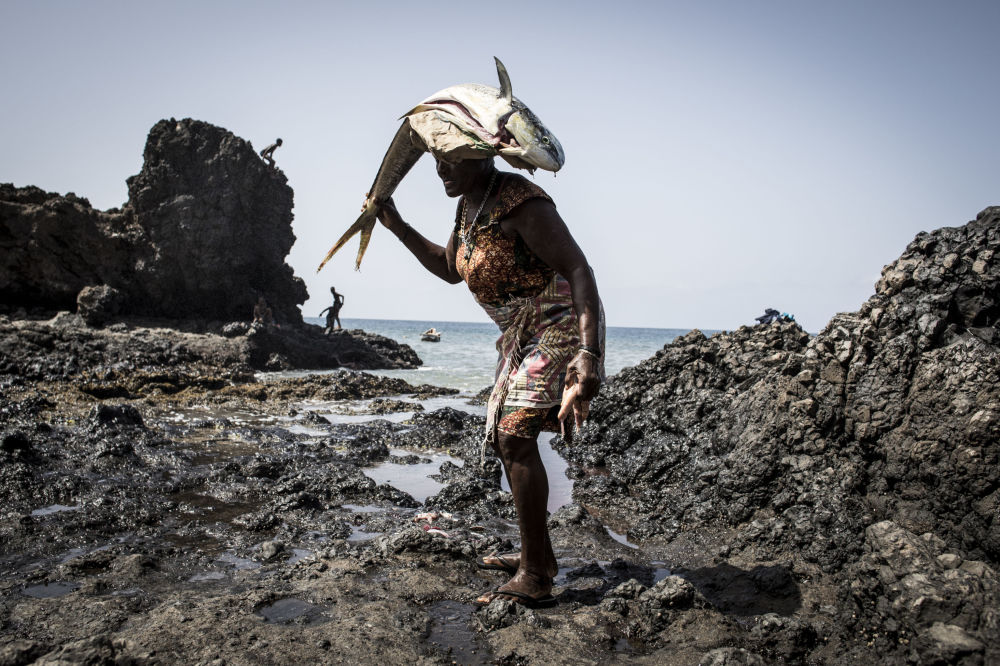 A woman carries a fish on her head after cleaning and gutting it in a small fishing village in Porto Mosquito, Cape Verde on October 8, 2019.