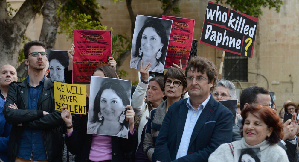 People hold portraits and placards as they attend a vigil in memory of murdered journalist Daphne Caruana Galizia in Malta