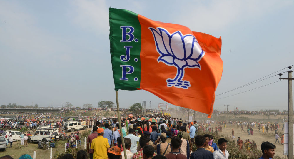 Indian supporters of the Bharatiya Janata Party (BJP) carry a party flag on their way to attend a campaign rally while wearing masks of Indian Prime Minister Narendra Modi ahead of the national elections in Siliguri on April 3, 2019