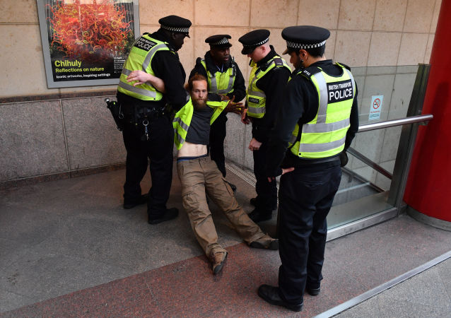 Police remove a protestor who had glued himself to the window of a DLR train at Canary wharf station on the third day of an environmental protest by the Extinction Rebellion group (File)