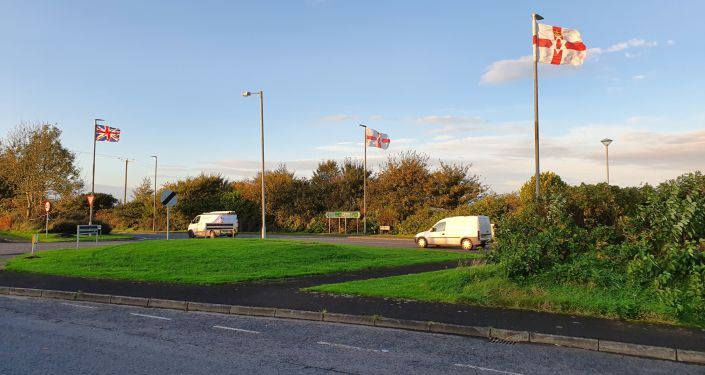 The union flag and the Northern Irish flag flutter on lampposts in a loyalist area on the Strabane to Londonderry road