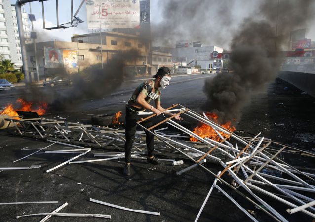 An anti-government protester adds to a makeshift barricade blocking a highway that links to northern Lebanon in east Beirut, Lebanon, Sunday, 20 October 2019