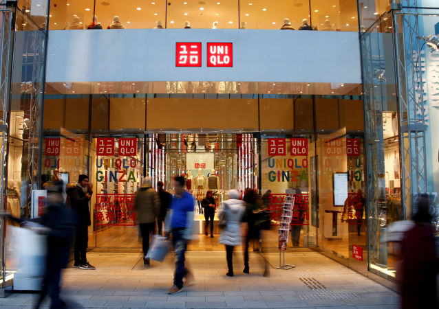 People walk past Japan's Fast Retailing Co Ltd's Uniqlo signboard at its shop in Tokyo, Japan January 12, 2017