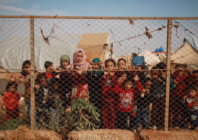 Displaced Syrian children stand behind a fence outside their tents in a camp set up near the village of Kafr Lusin, in Idlib's northern countryside near the Syria-Turkey border, on October 22, 2019.
