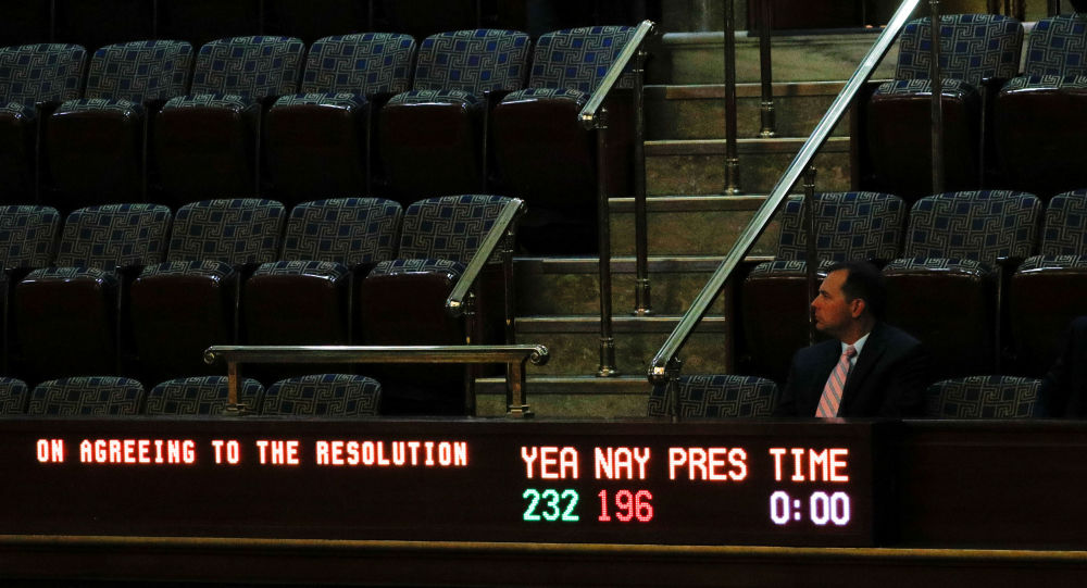 A man sits in the visitors gallery above the floor of the U.S. House of Representatives as a display board shows the final vote tallies of 232 Yea and 196 Nay on a resolution that outlines the next steps in the impeachment inquiry of U.S. President Donald Trump on Capitol Hill in Washington, U.S., October 31, 2019