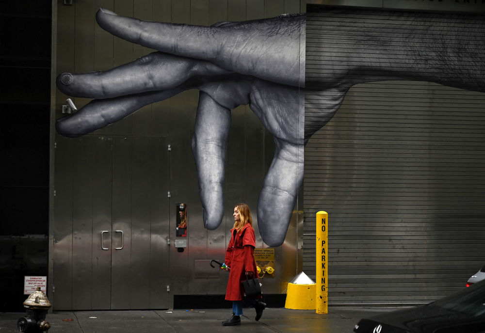 A woman passes a mural in Manhattan on October 27, 2019 in New York City.