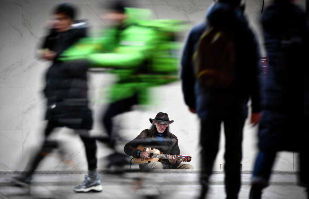 Sergei Sadov, a street musician, plays guitar at the entrance to a metro station in Moscow on October 30, 2019.