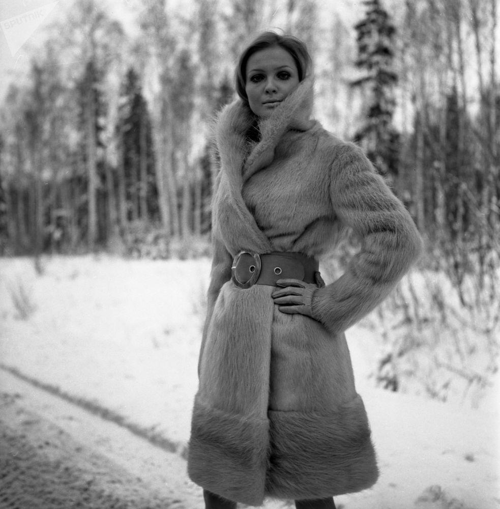 A woman wears an otter-skin coat in 1968