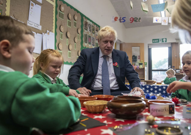 Britain's Prime Minister Boris Johnson makes pictures of fireworks with children at a school in Suffolk