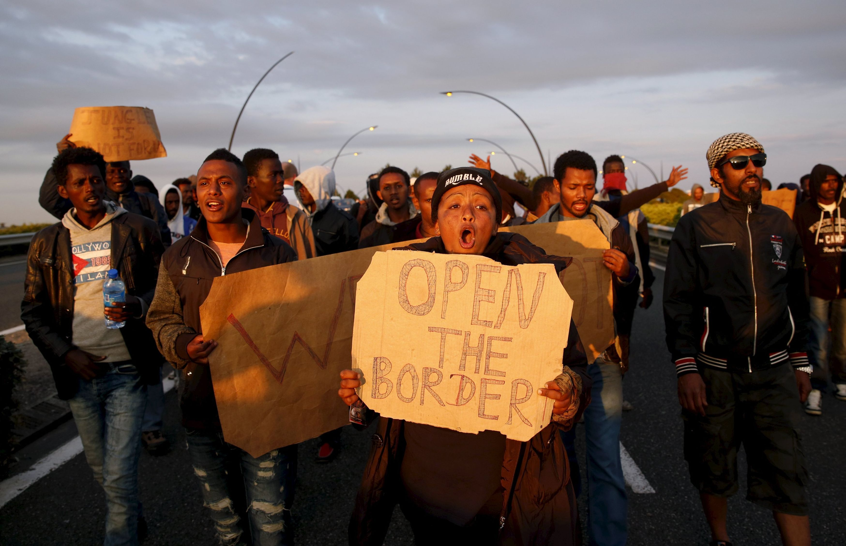 African migrants shout slogans during a protest on a motorway in Calais, France