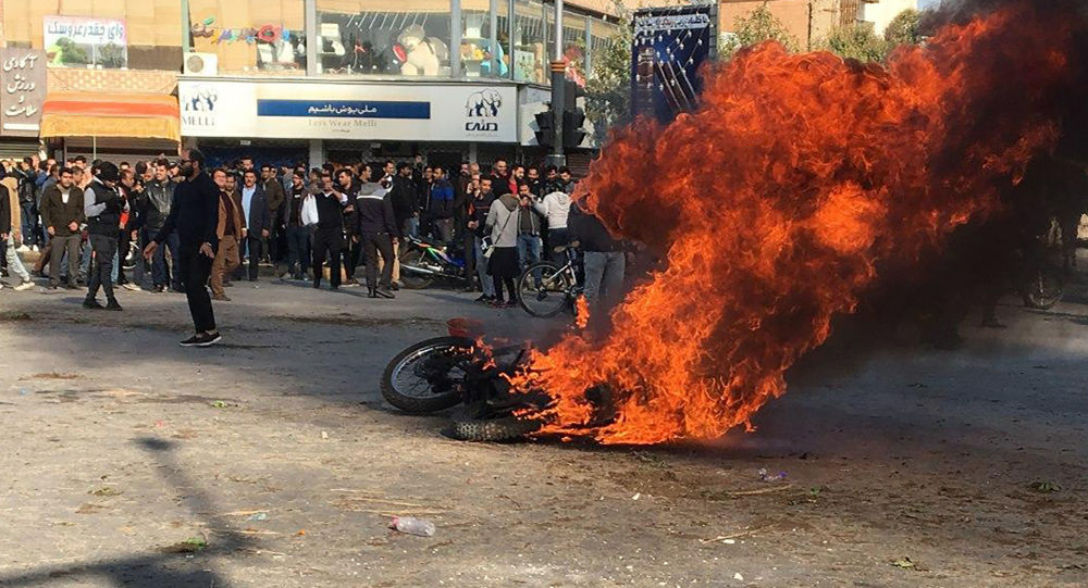 Iranian protesters gather around a burning motorcycle during a demonstration against an increase in gasoline prices in the central city of Isfahan, on November 16, 201
