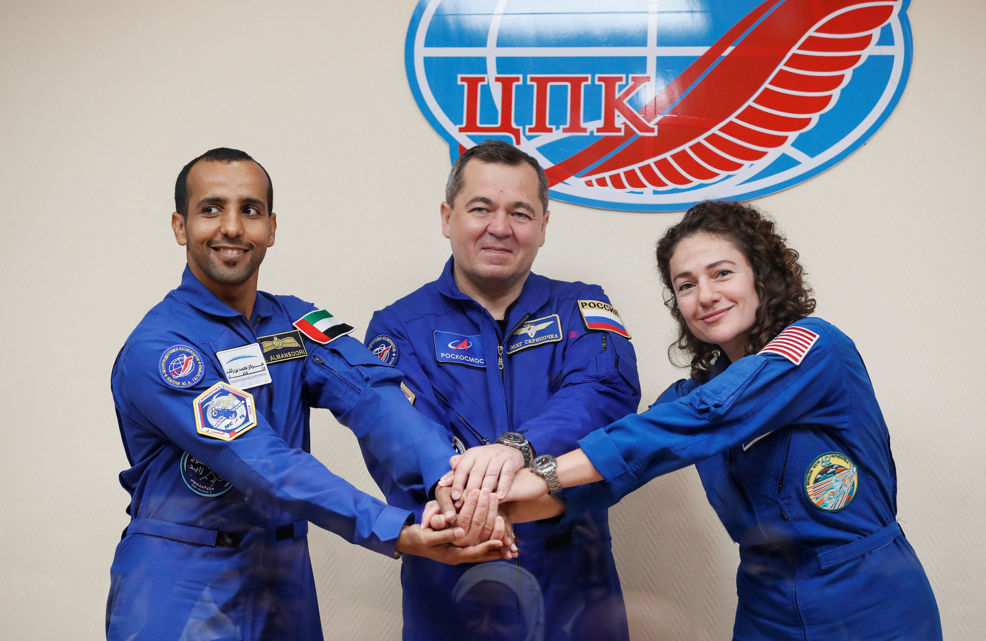 Crew members Jessica Meir of the U.S., Oleg Skripochka of Russia and Hazzaa Ali Almansoori of United Arab Emirates pose for a picture behind a glass wall during a final news conference ahead of their mission to the International Space Station (ISS) in Baikonur, Kazakhstan September 24, 2019