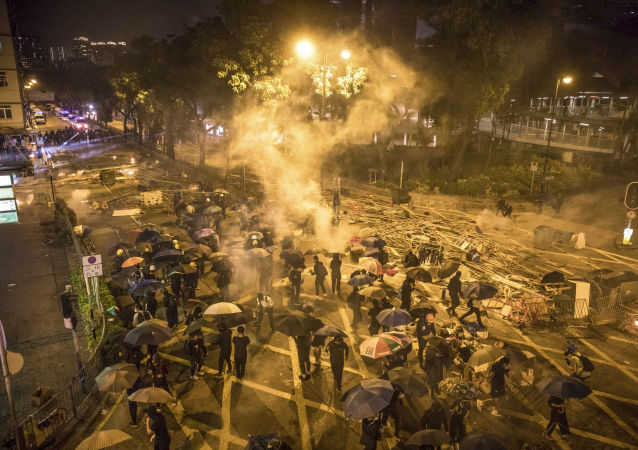 Protesters react as police fire tear gas while they attempt to march towards Hong Kong Polytechnic University in Hung Hom district of Hong Kong on November 18, 2019