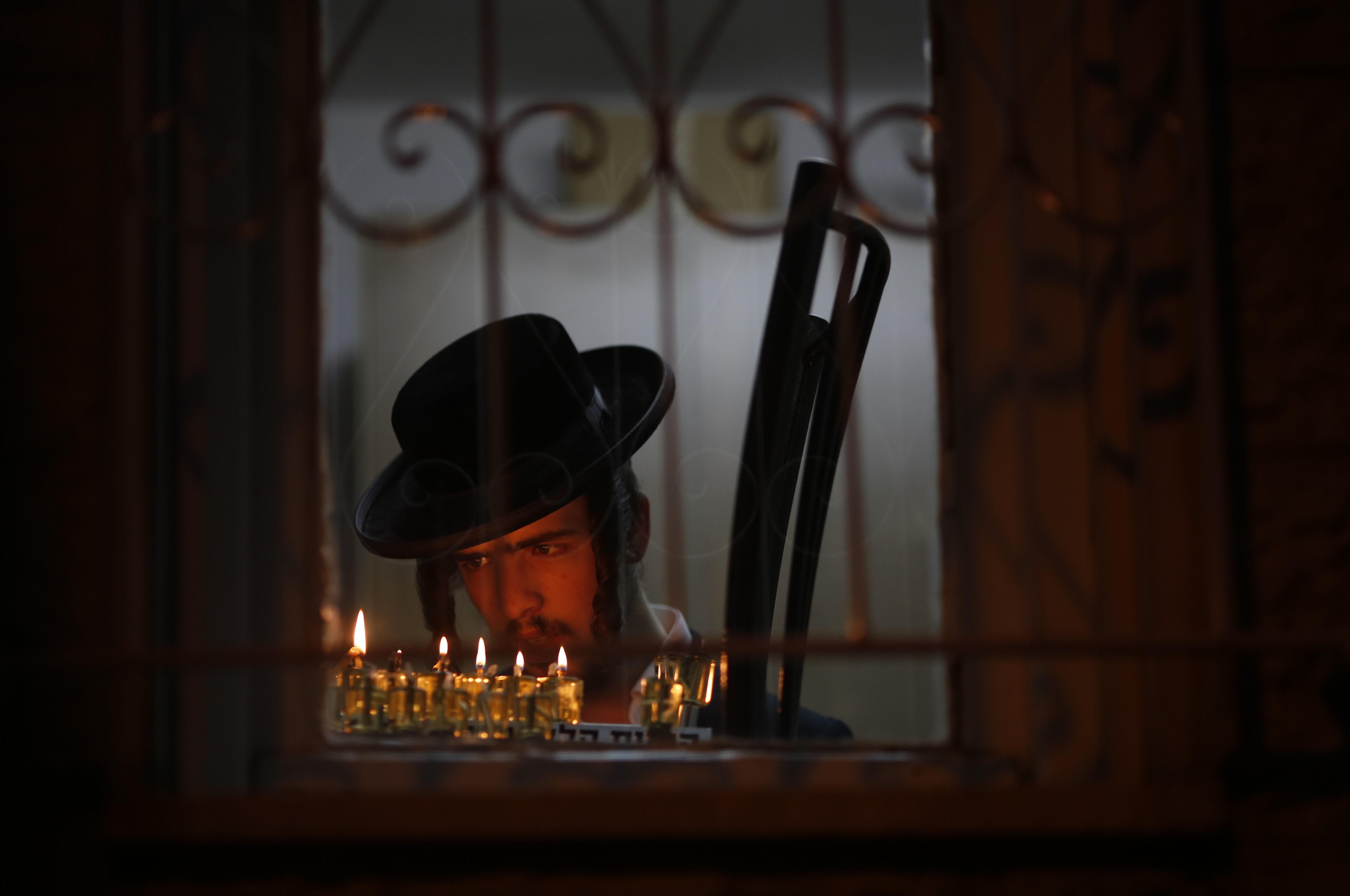An ultra-Orthodox Jewish man lights candles during the Jewish holiday of Hanukkah in Jerusalem's Mea Shearim neighborhood in Jerusalem, Sunday, Dec. 17, 2017