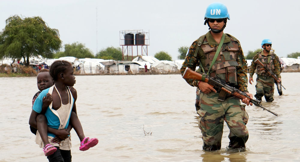 A girl holding a child walks past UN peacekeepers, after heavy rains and floods forced hundreds of thousands of people to leave their homes, in the town of Pibor, Boma state, South Sudan, November 6, 2019.