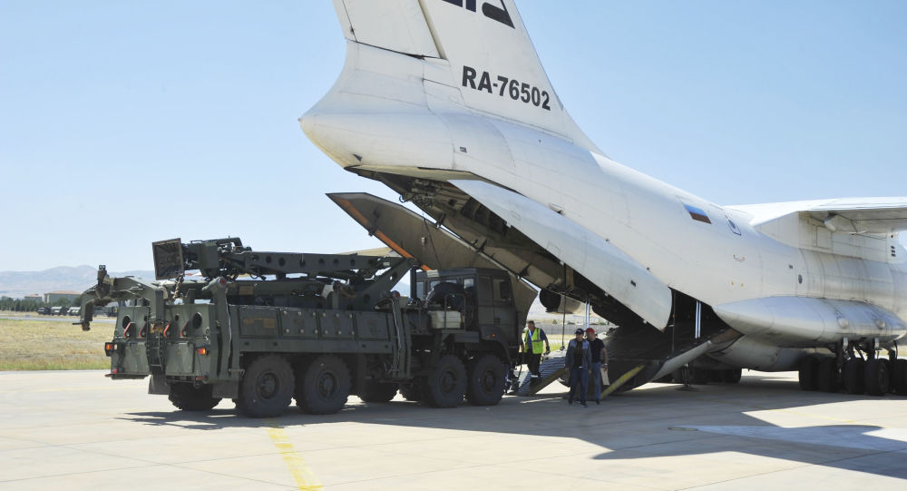 Military officials work around a Russian transport aircraft, carrying parts of the S-400 air defense systems, after it landed at Murted military airport outside Ankara