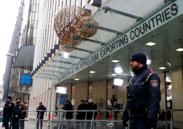 Journalists and police officers stand outside the Organisation of the Petroleum Exporting Countries (OPEC) headquarters in Vienna, Austria December 5, 2019.