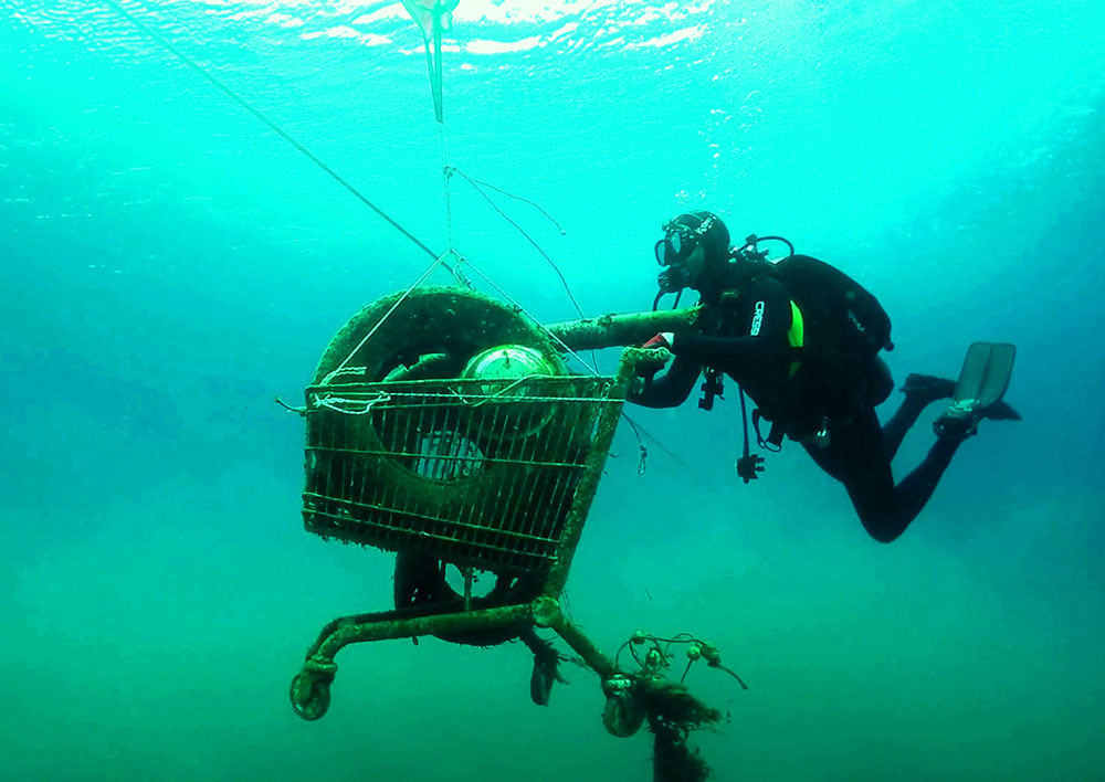 This picture released on November 30, 2019 by the Aegean Rebreath, a Greek organisation formed in 2017, shows volunteeres collecting a rusted shopping cart from the sea during an operation to protect Aegean biodiversity from waste, on the Ionian island of Zakynthos.