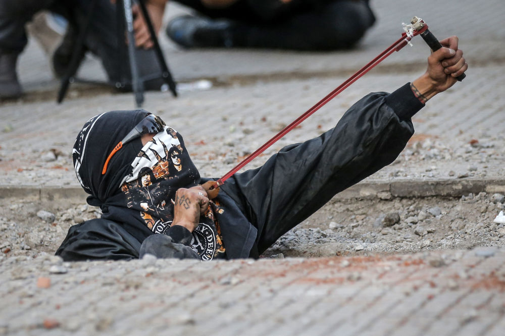 A feminist activist uses a slingshot during a protest against gender violence and patriarchy in Santiago on November 29, 2019.