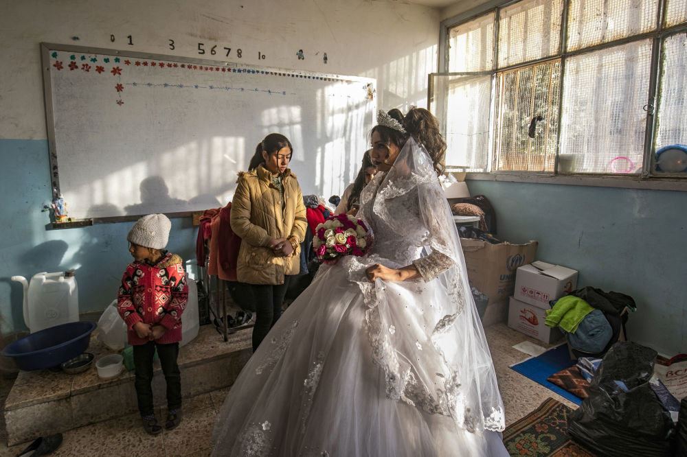 Hanan, a displaced Syrian woman wears her wedding dress at her temporary home, a school building transformed into a makeshift shelter, before being wed to Mohammad in the northern Syrian city of Hasakeh on December 1, 2019. Hanan and Mohammad fled with their families from the northeastern town of Ras al-Ain following the Turkish offensive against the Kurdish-dominated region, were wedded after being in love for three years.