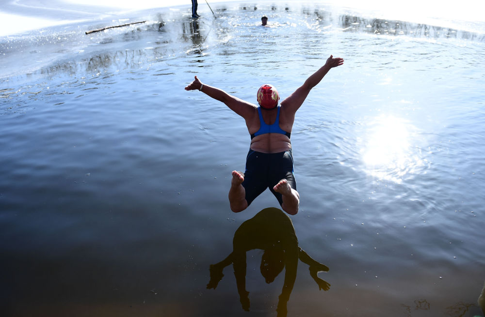 A woman jumps into a partly frozen lake at a park in Shenyang in China's northeast Liaoning province on December 2, 2019.