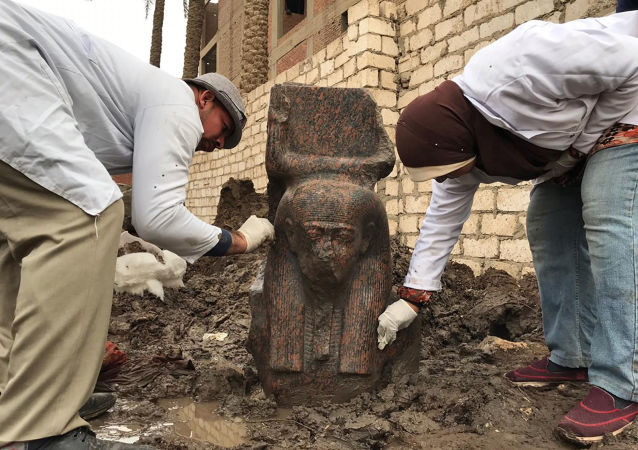 Archaeologists with a fragment of a statue of ancient Egyptian Pharaoh Ramesses II in the village of Mit Rahinah, Egypt