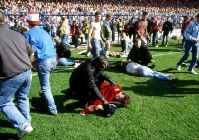 ** FILE ** In this April 15, 1989 file photo police, stewards and supporters tend and care for wounded supporters on the field at Hillsborough Stadium, in Sheffield, England.  British prosecutors will consider criminal charges against 23 suspects following separate investigations into the Hillsborough Stadium disaster in 1989 in which 96 soccer fans were killed, it was reported on Thursday, Jan. 12, 2017