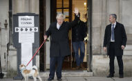 Britain's Prime Minister and Conservative Party leader Boris Johnson with his dog Dilyn leaves after voting in the general election at Methodist Central Hall, Westminster, London, Thursday, Dec. 12, 2019.