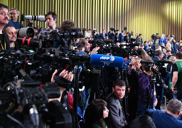 Journalists wait before the start of the Russian President Vladimir Putin's annual news conference, in Moscow, Russia
