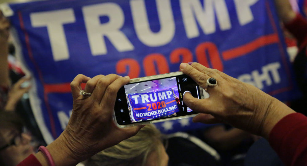 Supporters of President Donald Trump photograph a banner before a panel discussion with Donald Trump, Jr., Trump campaign senior adviser Kimberly Guilfoyle, and Trump campaign manager Brad Parscale, Tuesday, Oct. 15, 2019, in San Antonio.