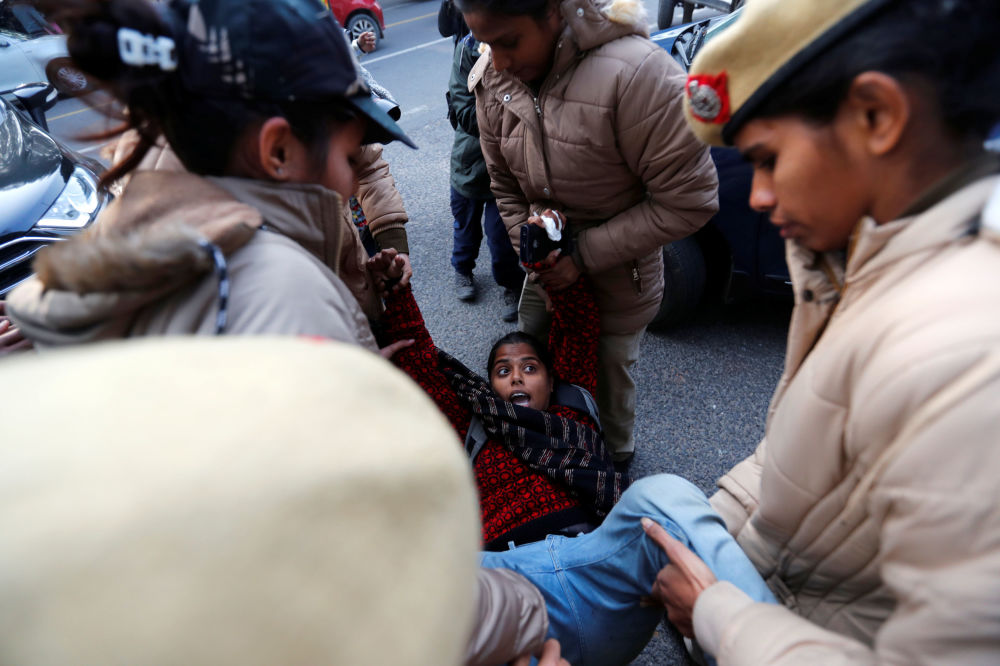 A demonstrator is detained by police outside the Assam bhawan (building) during a protest against India's new citizenship law in New Delhi, 23 December 2019.